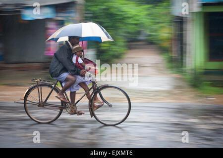 Padre e hija ciclista en SIGIRIYA durante la tormenta de lluvia de monzón Imagen De Stock