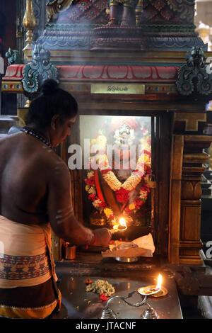 Sacerdote con un arthi alcanfor (iluminados) realizar mañana ceremonia puja, Sri Thendayuthapani templo hindú (Chettiars' Templo), Singapur, sudeste de As Imagen De Stock