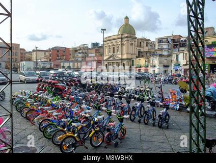 Las bicicletas de niños para la venta en Piazza Mercato en Nápoles con la iglesia de Santa Croce e Purgatorio Imagen De Stock