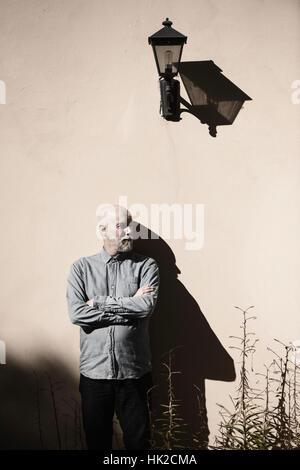 Y seria cool viejo hombre de pie delante de la pared. Sol y Sombra gruesa. Exterior El edificio con espacio de copia. Imagen De Stock