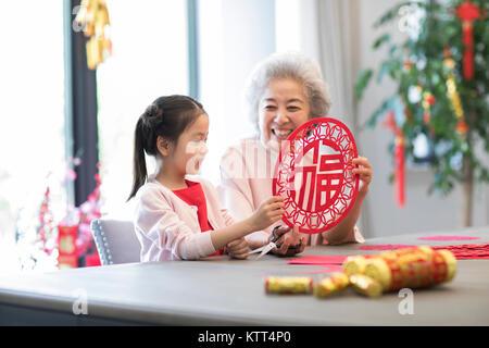 Nieta y abuela con el Año Nuevo chino del recorte de papel Imagen De Stock