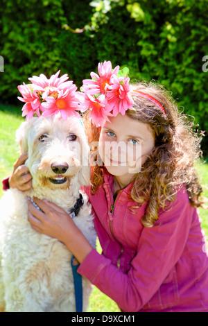 Jovencita y perro blanco vestidos de flores Imagen De Stock