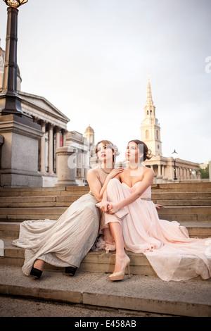 Retrato de dos mujeres modelos posando en pasos, Trafalgar Square, Londres, Reino Unido. Imagen De Stock