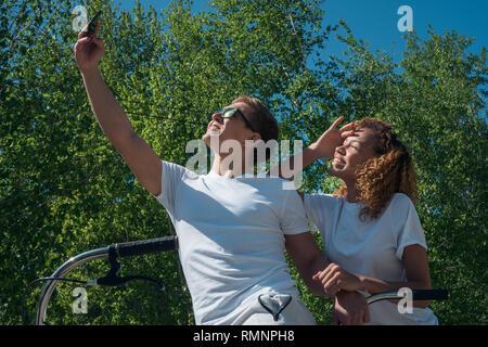 Un par de amigos un chico y una chica tome un selfie sobre un paseo Imagen De Stock