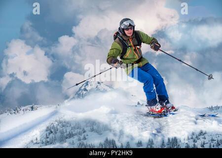 Componer de aparentemente gigante país atrás esquiador, que cabalga las montañas coronadas de nieve. Imagen De Stock