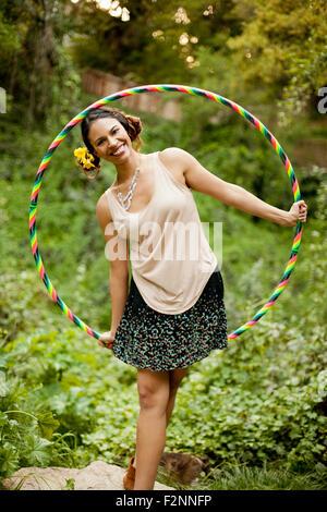 Mujer de raza mixta jugando con aro de plástico Imagen De Stock