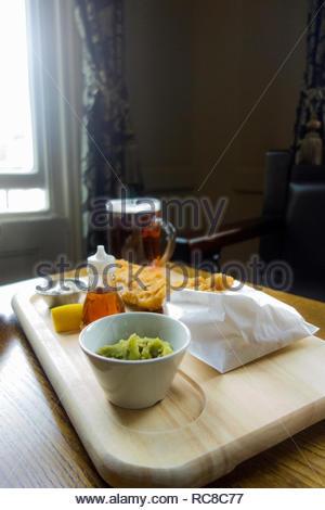 Bodegón de pescado y papas fritas y puré de guisantes comida de pub y una pinta de cerveza en el pub tabla Imagen De Stock