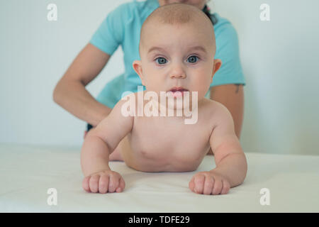 Retrato de un pequeño y lindo bebé con grandes ojos hermosos. Una mujer que hace masaje a un niño pequeño. Masaje para bebés Imagen De Stock