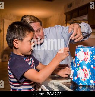 Niño Pequeño envoltorio de regalo de Navidad. Con la ayuda de abuelo serie de 7 imágenes. Señor © Myrleen Pearson ...Cate Ferguson Imagen De Stock