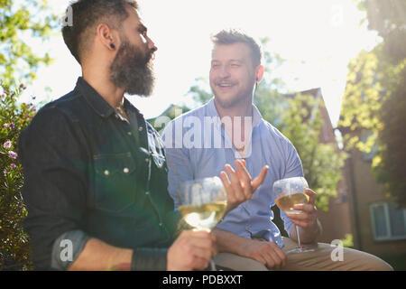 Una pareja gay masculina sonriente bebiendo vino blanco en el soleado jardín Imagen De Stock