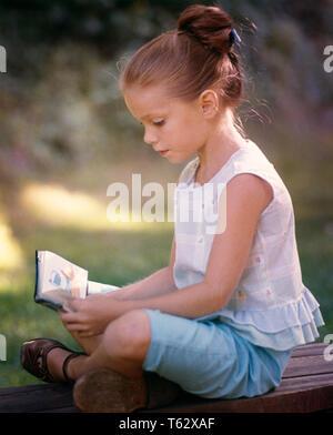 1960 Pretty Little Girl Blue SHORTS SIN MANGAS con las piernas cruzadas sentado leyendo libros - kj3408 FTZ001 HARS PENSATIVO FOCUS verano bastante tranquilo UPDO ELEGANTE ZEN intenso crecimiento centrados menores ETNIA CAUCÁSICA INTENCIÓN ANTICUADO SLEEVELESS Imagen De Stock