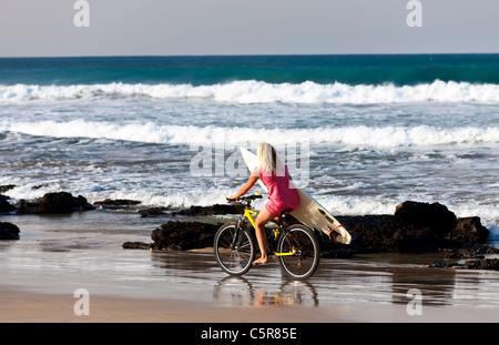 Una rubia surfer girl paseos por la playa con las olas. Imagen De Stock