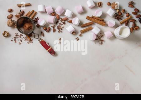 Ingredientes de chocolate caliente. Blanco Rosa big marshmallow, granos de cacao, el cacao en polvo, la canela, el chocolate, las nueces picadas sobre fondo de mármol blanco. Imagen De Stock