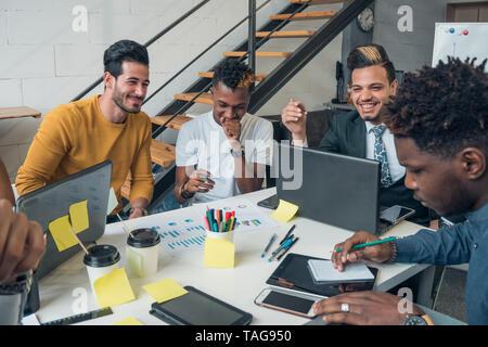 La comunicación internacional. Jóvenes de diferentes nacionalidades comunicarse y reír en la oficina. Imagen De Stock