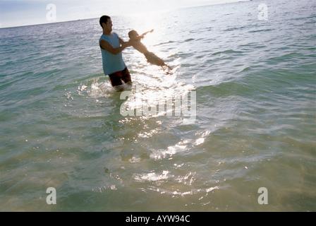 Padre sosteniendo a su hijo en el aire en el océano Imagen De Stock
