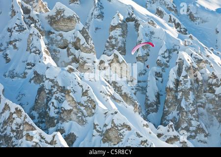 Un piloto de parapente volando pasado una impresionante formación rocosa en la montaña. Imagen De Stock