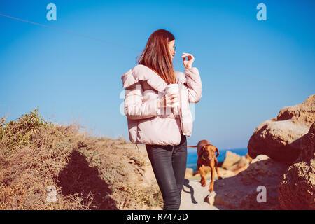 Mitad mujer adulta en la playa paseando a su perro, Odessa, Odeska Oblast, Ucrania Imagen De Stock