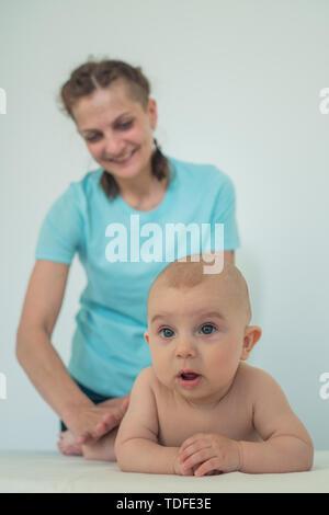 Retrato de un niño con un gracioso sorprendió riendo mujer en el fondo. Imagen De Stock