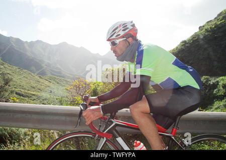 Hombre en bicicleta a lo largo de una carretera de montaña, Tenerife, Islas Canarias, España Imagen De Stock