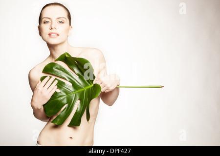 Modelo cubriendo los pechos con hoja grande Imagen De Stock