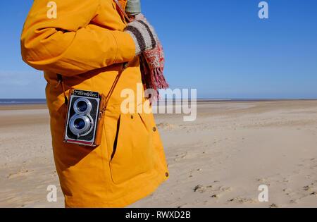 Persona que transporta vintage retro cámara sobre el hombro, holkham Beach, North Norfolk, Inglaterra Imagen De Stock