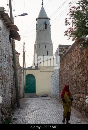 Harari mujer pasa delante de una mezquita, Región Harari, Harar, Etiopía Imagen De Stock