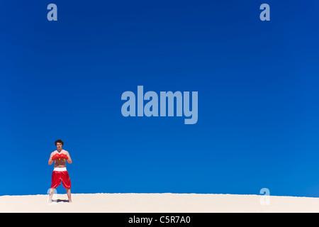 El boxeador se levanta sobre una duna de arena guantes conectado listo para la acción. Imagen De Stock