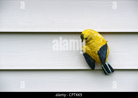 Cerámica una talla de un pequeño pájaro amarillo, aferrándose a la pared blanca. Imagen De Stock