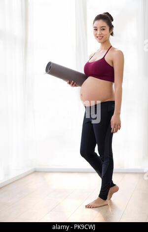Alegre gestante con estera del yoga Imagen De Stock