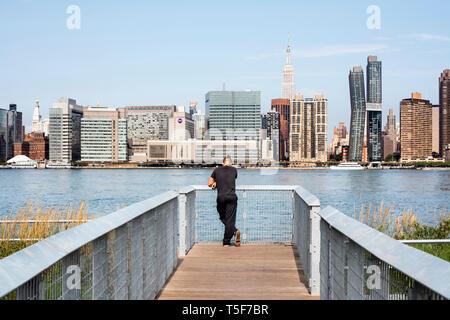 Visitante en un puente sobre los humedales, con vistas al East River y Midtown Manhattan. Hunters Point South Park, Nueva York, Estados Unidos. Arquitecto: Imagen De Stock