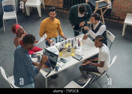 Comunicación en vivo de un grupo de jóvenes en la oficina. Reunión empresarios prometedores en la oficina con un diseño moderno. Imagen De Stock
