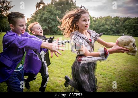 Los niños chase una niña vestida como un zombi prom queen para la noche de Halloween. Imagen De Stock