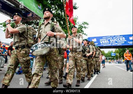 Un grupo de soldados cruzan la línea de meta mientras toca instrumentos durante el primer día.Ya que es el más grande del mundo multi-día caminando, el evento de cuatro días de marzo es visto como el primer ejemplo de deportividad y pegado internacional entre militares y civiles y de las mujeres de muchos países diferentes. Los participantes en la 103ª comenzaron los cuatro días marchas en Nijmegen, en la Wadren a las 4am, cruzaron el puente Waalbrug (la legendaria de Nijmegen), y pasando por la ciudad de Elst (el día), donde el color oficial era azul. El día era frío, con temperaturas bajas t Imagen De Stock