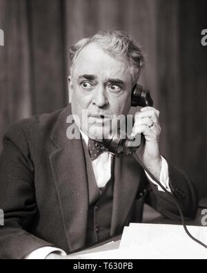 Hombre de negocios de 1930 escucha en el teléfono con alarmado consternado preocupado la expresión facial - t3549 HAR001 HARS NOSTALGIA vieja moda 1 COMUNICACIÓN IRA FACIAL SHOCK CONMOCIONADO PROBLEMAS PROBLEMA LIFESTYLE ELDER EMPLEOS MANAGER copia de media longitud espacial personas reflexivas hombres ejecutivos senior de riesgo hombre adulto SENIOR B&W TRISTEZA OCUPACIÓN VENDIENDO OLDSTERS antiguas ocupaciones político aturdido preocupación política teléfonos ancianos jefes teléfonos procurador centró intenso BLANCO Y NEGRO VENDEDORES GESTORES DE ETNIA CAUCÁSICA HAR001 INTENCIÓN ANTICUADO Imagen De Stock