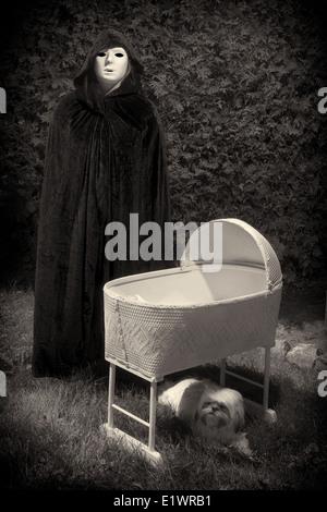 Cintage mirando la foto de un escalofriante enmascarado y disfrazado persona junto a un misterioso, cuna vacía. Imagen De Stock