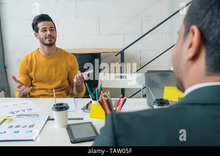 Un joven es entrevistado para un trabajo. Guy's a hablar con su jefe en la oficina. La comunicación empresarial. Imagen De Stock