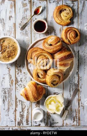 Variedad de bollos de hojaldre casera rollos de canela y croissant servido con taza de café, mermelada, mantequilla como desayuno sobre fondo blanco tablón de madera. Imagen De Stock