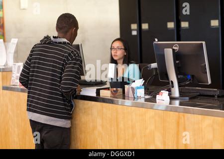 Estudiante africano pidiendo bibliotecario asiática una pregunta en la universidad. Imagen De Stock