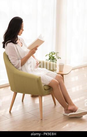 Alegre mujer embarazada libro de lectura en casa Imagen De Stock