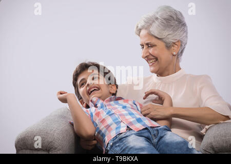 Abuela y nieto jugando en el sofá Imagen De Stock