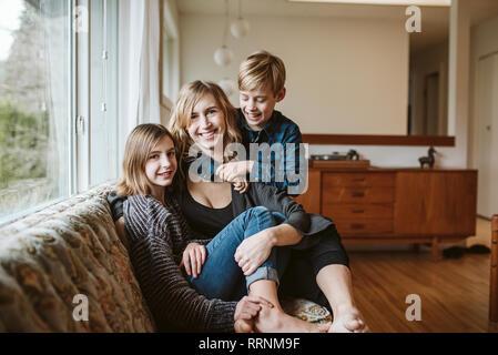 Retrato feliz madre e hijos caricias en el sofá de la sala Imagen De Stock
