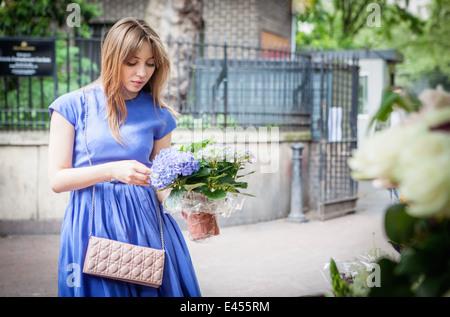 Mujer joven recogida de planta en maceta Imagen De Stock