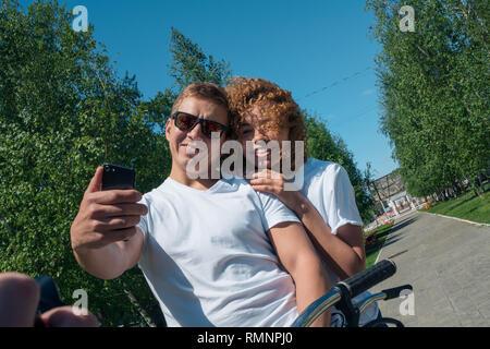 Amigos un chico y una chica tome un selfie en un paseo en el verano y una sonrisa Imagen De Stock