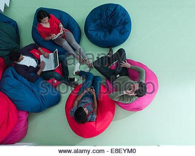 Los hombres y las mujeres que usan laptop y celulares en bean bag sillas Imagen De Stock