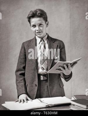1930 Chico vistiendo un traje y corbata de lectura permanente desde portátiles recitar en la escuela - s3320 HAR001 HARS contacto ocular escuelas traje y corbata EL GRADO Y LA AUTORIDAD PRIMARIA OCUPACIONES ELEGANTE CONFÍA EN LA COOPERACIÓN grado K-12 escuela pre-adolescentes menores de crecimiento pre-teen BOY RECITANDO EN BLANCO Y NEGRO la etnia CAUCÁSICA HAR001 anticuado hablar en público. Imagen De Stock