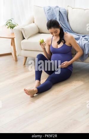 Mujer embarazada alegre celebración de una manzana Imagen De Stock