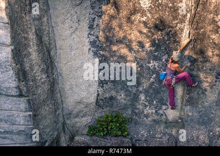 Las hembras jóvenes de escalador escalada cara, un alto ángulo de visualización, humo Bluffs, Squamish, British Columbia, Canadá Imagen De Stock