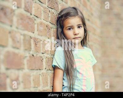 Niña de 5 años de edad, apoyado contra una pared, retrato, Alemania Imagen De Stock