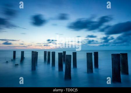 Viejo Muelle pilotes al atardecer sobre el Golfo de México, Naples, Florida, EE.UU. Imagen De Stock