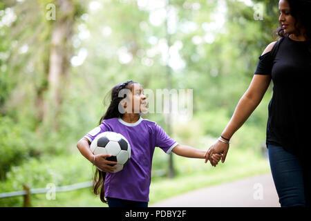 Madre e hija afectuosa con las manos la pelota de fútbol Imagen De Stock